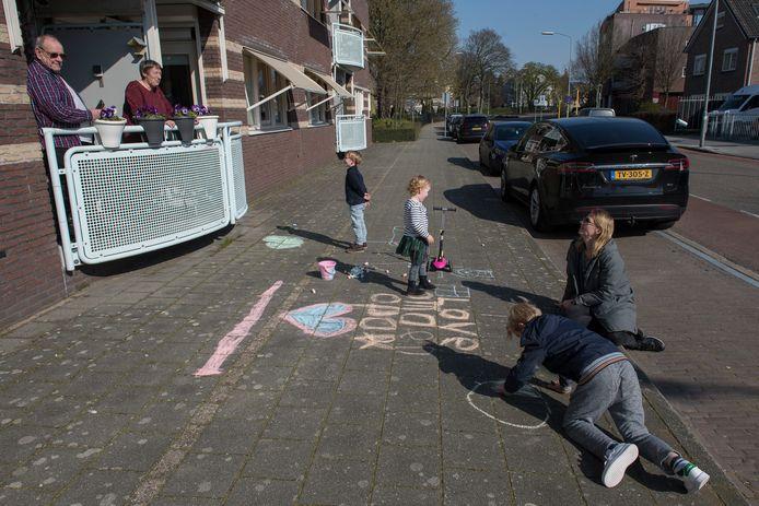 Henk en Mieke van der Heijden hebben vanaf hun balkon contact met hun kleinkinderen, die ervoor spelen.