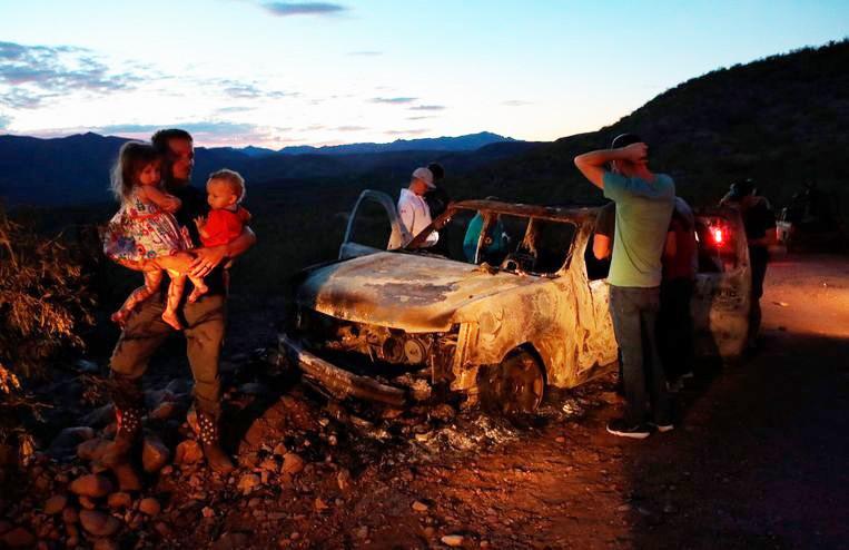 Familieleden treuren bij de uitgebrande wagen na de aanslag