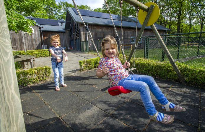Lisa en Ilse (op de schommel) spelen buiten bij 't Stieltjen. In het kulturhus in Haarlo liggen bijna alle activiteiten stil. Er is alleen nog kinderopvang voor ouders in cruciale beroepen.