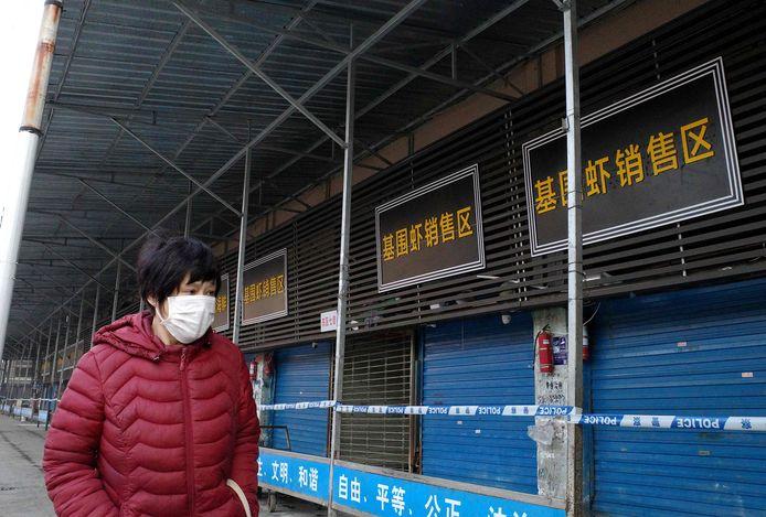Une femme marchant devant le marché au poisson de Wuhan, qui a été fermé depuis le début de l'épidémie.