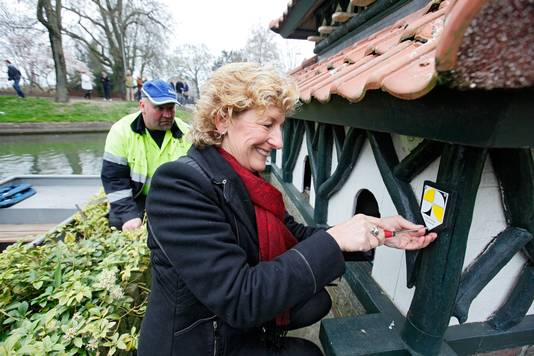 Archieffoto: Wethouder Corry van Rhee bevestigt het eerste gemeentelijke monumentenbordje op het eendenverblijf in de Tielse Stadsgracht.