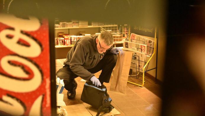 Een rechercheur onderzoekt een tas die de daders van de overval in Driebergen mogelijk hebben achtergelaten.