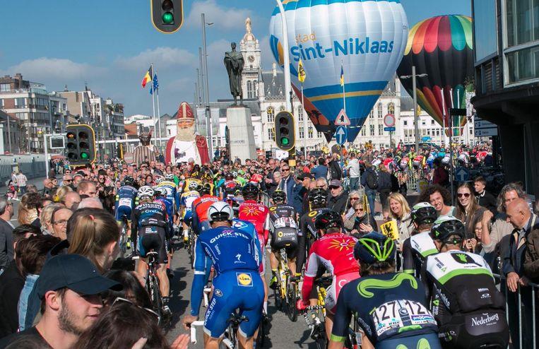Tom Boonen (centraal in het blauw) draait in het peloton de Grote Markt op, waar luchtballons en reuzen de Ronde-karavaan verwelkomen.