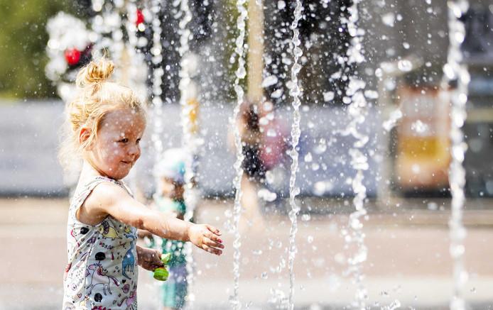 Een meisje speelt in een fontein op het Haarlemmerplein in Amsterdam op een bloedhete dag