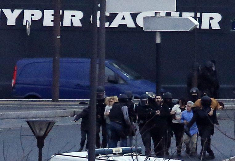 De politie bevrijdt gegijzelden uit de Joodse supermarkt in Parijs. Beeld afp
