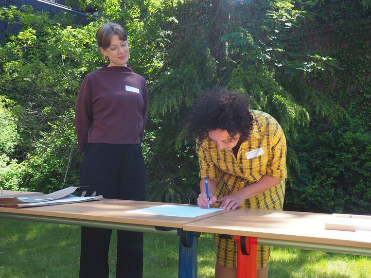 Mechels schepen Gabriella De Francesco ondertekent het charter. Naast haar staat Esther Schenk, stafmedewerker gezondheidsbevordering van LOGO Mechelen.