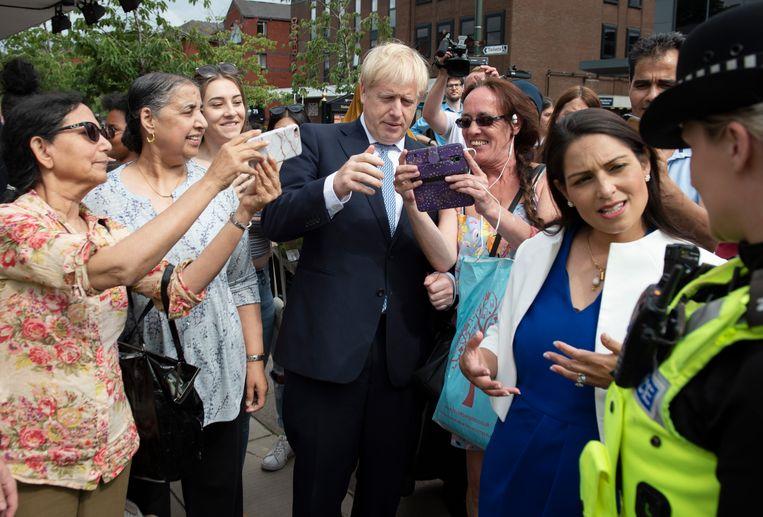 Premier Boris Johnson en minister Priti Patel vrijdag 26 juli op werkbezoek in Birmingham.  Beeld Getty Images