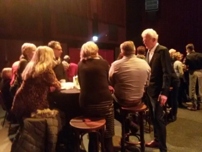 Peter van der Burgt (rechts) spreekt aan een tafeltje met zijn patiënten.