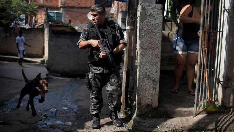 Een politie-inval in de sloppenwijken van Rio de Janeiro. De hond is overigens niet Boss zelf. Beeld AP