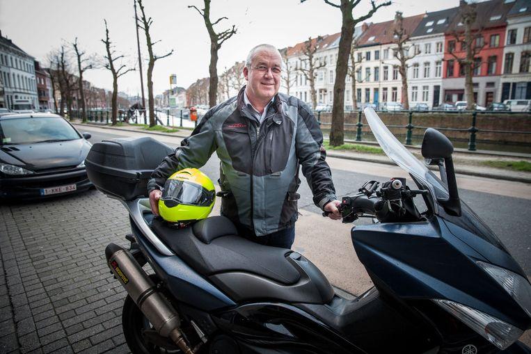 Jozef Burm bij de scooter waarmee hij zijn huisbezoeken aflegt.