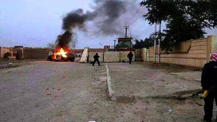 Een uitbrandende auto in Mosul Beeld null