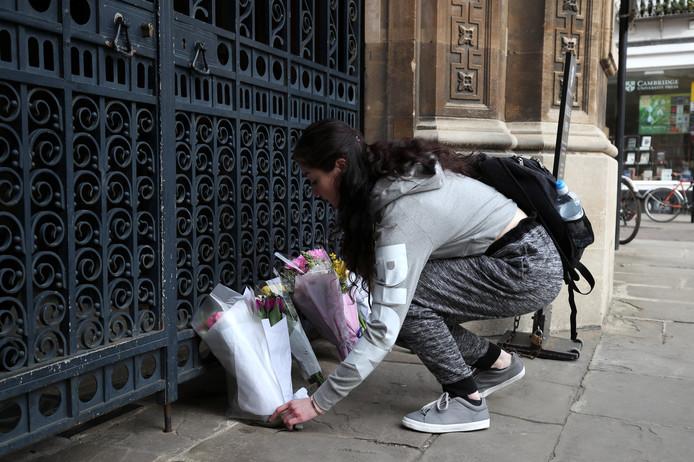 Een vrouw laat bloemen achter bij de universiteit van Cambridge, waar Hawking studeerde