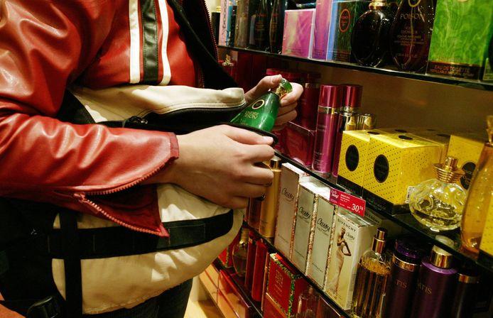 Kostbare flesjes eau de toilet verdwijnen in de ruime tas van een winkeldievegge. Foto ter illustratie.