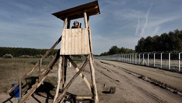 Hongaarse soldaat in wachttoren aan de grens die met een hek is afgesloten voor vluchtelingen Beeld null