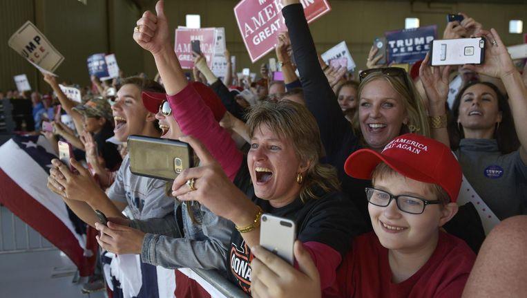 Aanhangers van Trump wachten de presidentskandidaat op in een vliegtuighangar in Minneapolis. Beeld afp