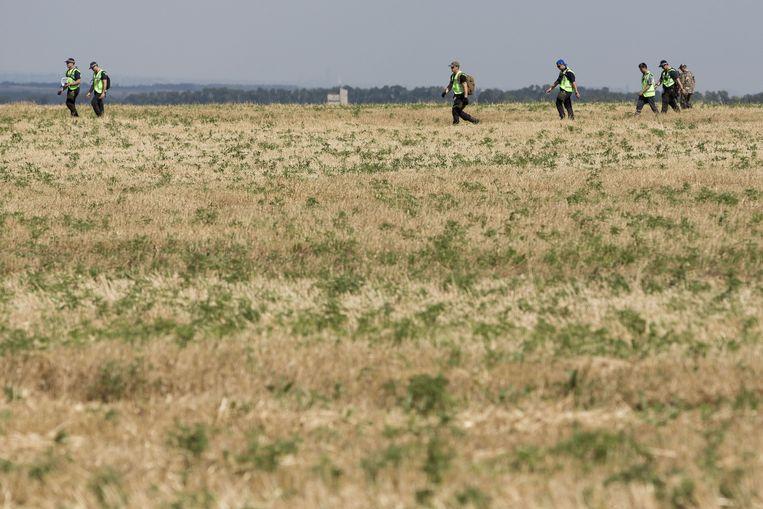 Forensisch onderzoekers doorzoeken het rampgebied van de MH17. Beeld anp