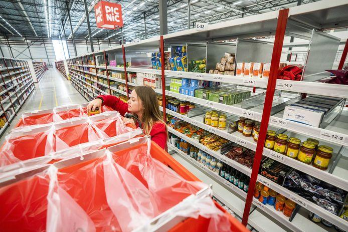 Een medewerker verzamelt producten in de schappen van het distributiecentrum van websupermarkt Picnic.
