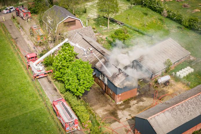 De brandweer blust de schuurbrand aan de Parallelweg in Overberg.