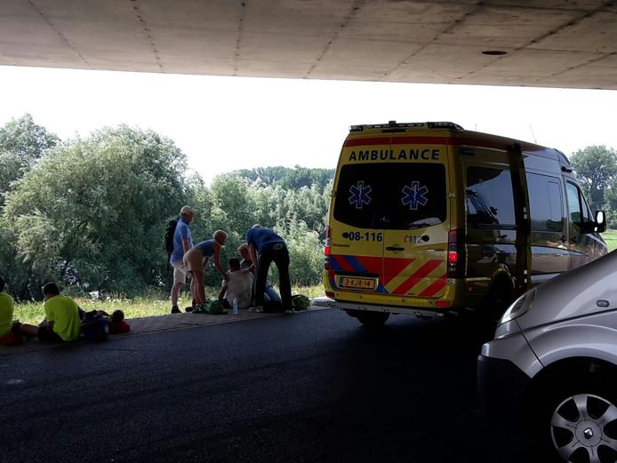 Onder de brug op de Oosterhoutsedijk worden verschillende mensen geholpen die bevangen zijn door de hitte.