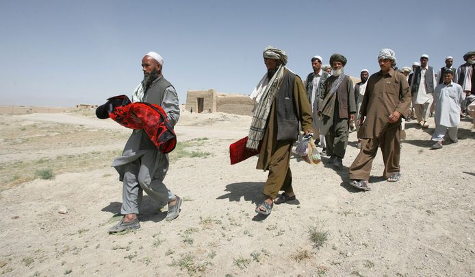 Familieleden rouwen om een verloren familielid, dat omkwam in gevechten tussen de Taliban en beveiligers van een NAVO-transport.