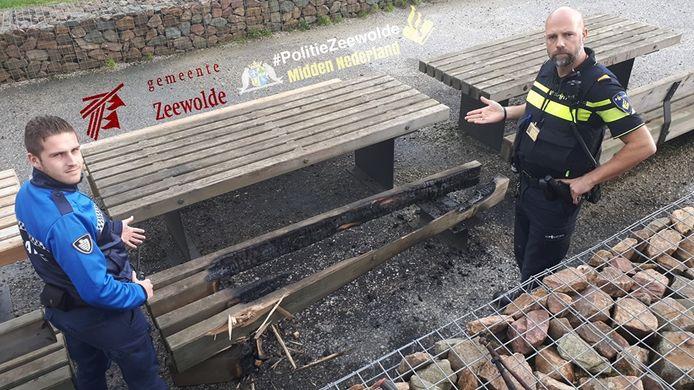 Politieagenten nemen een dag na de brandstichting een kijkje bij de afgebrande picknicktafel in Zeewolde.