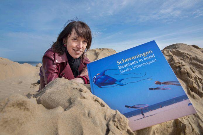 Sandra Uittenbogaart met haar eerste boek op de plek waar ze het liefst fotografeert: het Scheveningse strand.