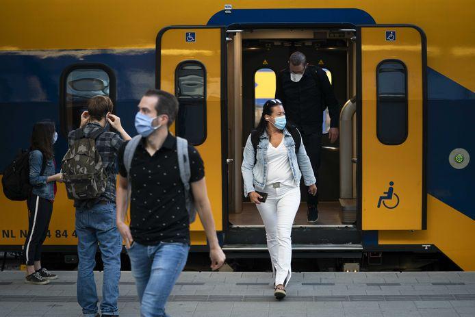 Reizigers met mondkapjes op het perron van Utrecht Centraal. De treinen rijden weer volgens de reguliere dienstregeling, nu het coronavirus over de piek heen is.