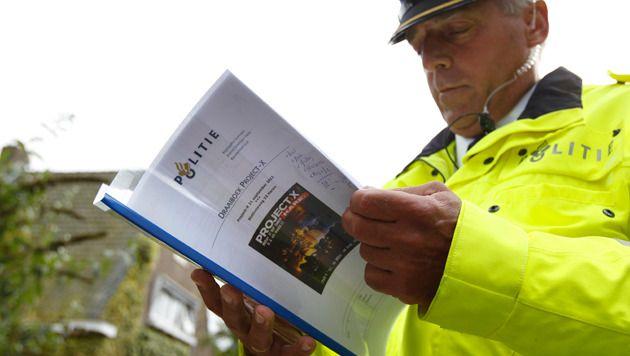 Een agent bekijkt het draaiboek voor Project X-feest.