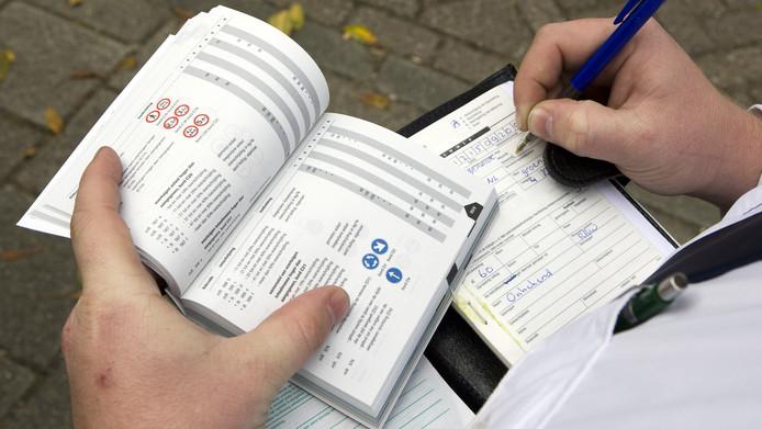 Politieagent schrijft een boete uit in 2009. Tegenwoordig worden bonnen uitgeschreven in een handcomputer.