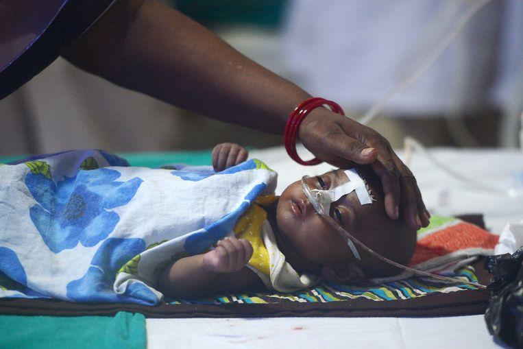 Een moeder verzorgt haar kind in het Baba Raghav Das ziekenhuis in Gorakhpur, een hospitaal dat vorige maand in opspraak raakte door tientallen sterfgevallen, vermoedelijk als gevolg van gebrek aan zuurstof.  Beeld AFP