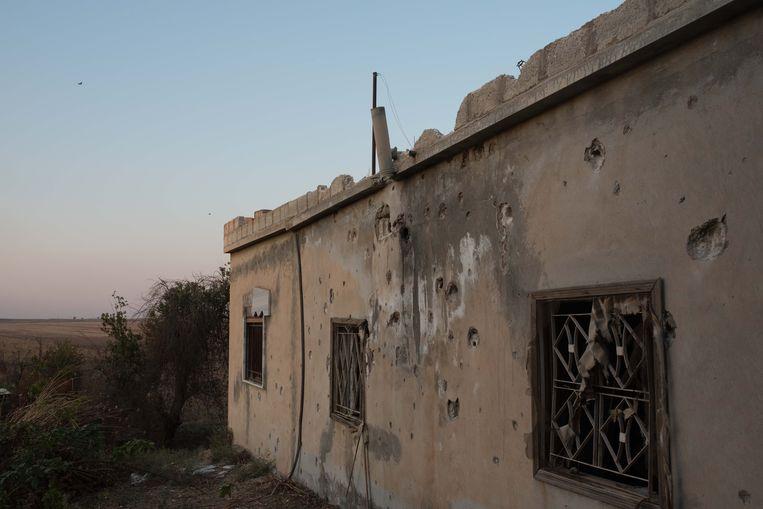 Een met kogels doorboord huis in het verlaten dorp Tel Tawil, waar gevechten tussen christelijke milities en Turkse troepen plaatsvinden. Beeld Vincent Haiges