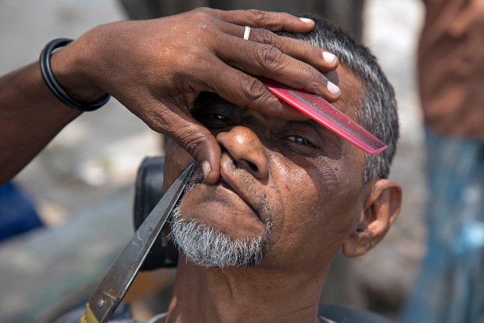 Een Bengaalse straatkapper werkt de snor van een klant bij langs de weg in Dhaka. Foto Monirul Alam