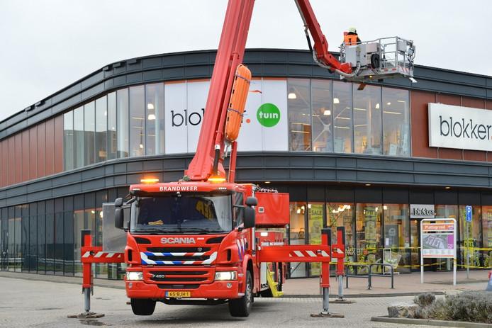 Een stuk dak wordt losgemaakt bij de Blokker aan de Kruisvoort in Breda.