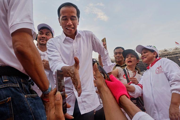 President Widodo tijdens zijn campagne, tussen aanhangers in Jakarta.   Beeld Getty Images