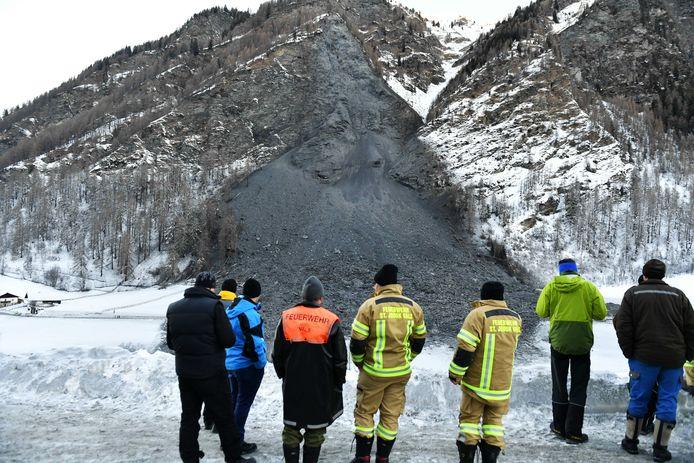 Reddingswerkers kijken naar de enorme modderstroom die de toegangsweg naar Vals volledig heeft geblokkeerd.