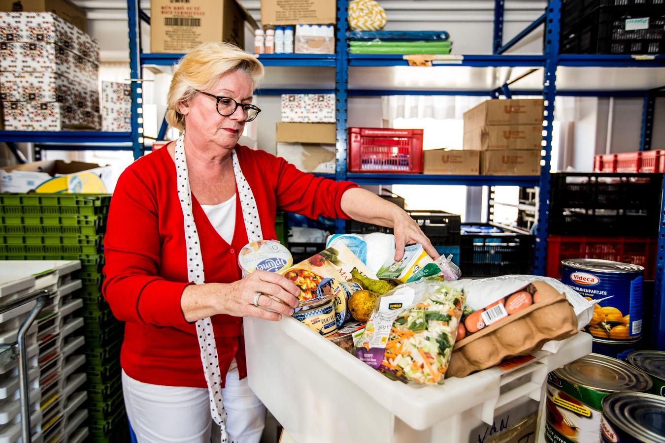 Thea van Amersfoort, voorzitter van de Voedselbank Heerde Epe Vaassen pakt een voedselpakket in.
