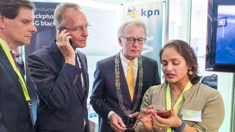 Minister Henk Kamp van Economische Zaken en burgemeester Jozias van Aartsen van Den Haag bekijken de nieuwe Blackphone van KPN. Beeld anp