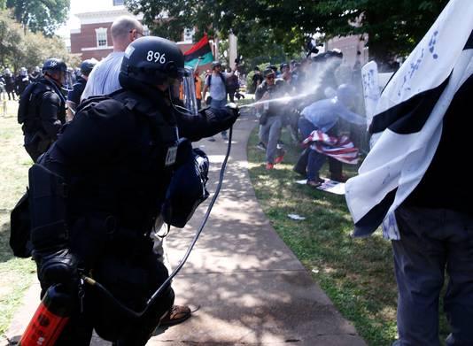 Politieagenten komen met pepperspray tussen twee groepen demonstranten.