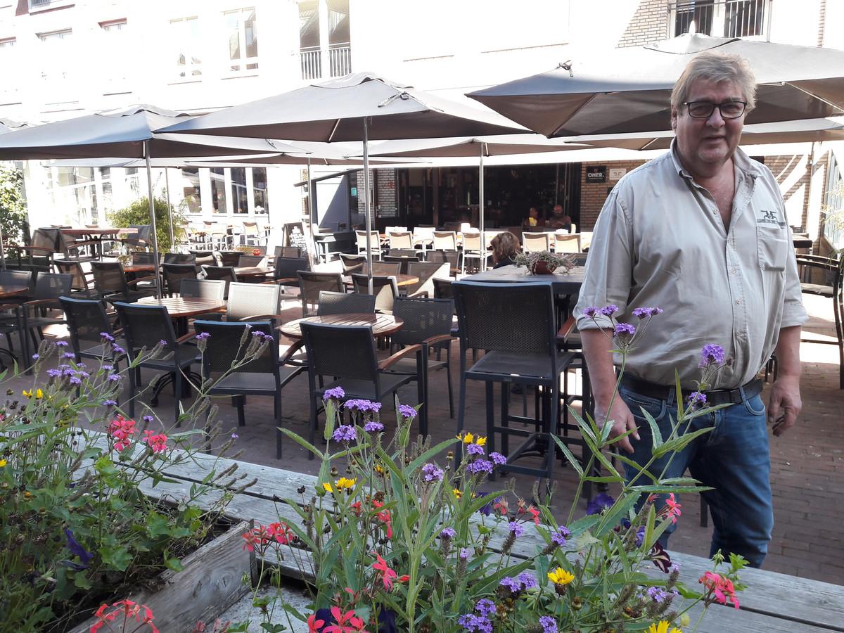 Toon Coppens, kastelein van 't Gelagh, voor een leeg terras van zijn zaak aan het Lindeplein in Oisterwijk. Op de voorgrond de bloembakken waarmee de ondernemers de defecte watertafels op hebben willen fleuren.