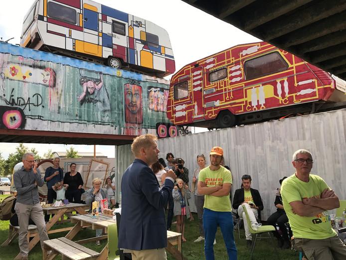 Wethouder Diepenveen opent de caravantoren van kunstenaar Pet van de Luijtgaarden (met oranje pet). Helemaal boven de caravan die Diepenveen beschilderde.