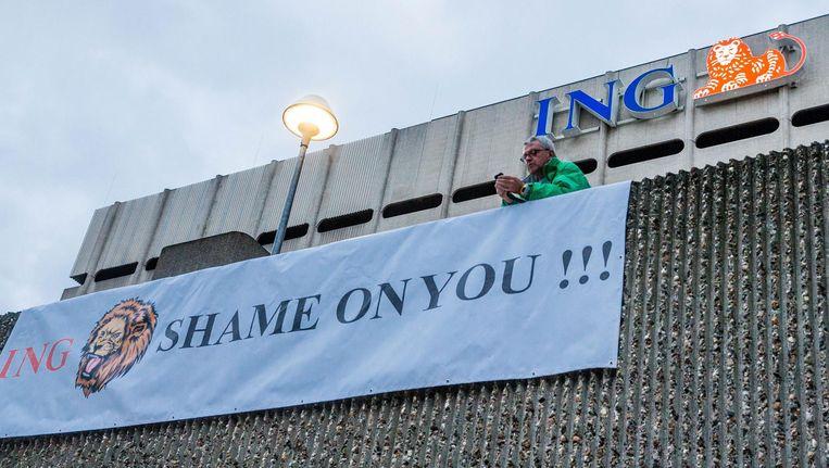 Vakbonden hebben uit protest tegen het grote aantal geschrapte banen een spandoek opgehangen bij het ING-hoofdkwartier in Brussel. Beeld anp
