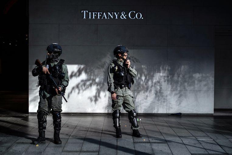 Politieagenten waken over Tiffany-filiaal in Hongkong.  Beeld Getty
