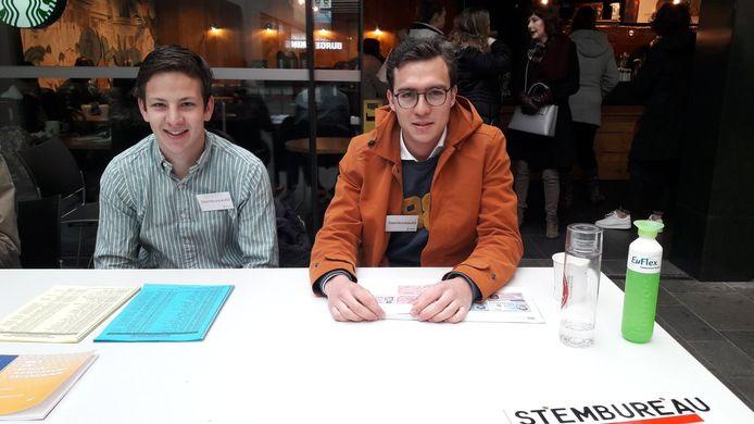Daan Hommersom (links) en Jelle Teusink verdienen bij het stembureau wat geld bij voor hun vereniging.