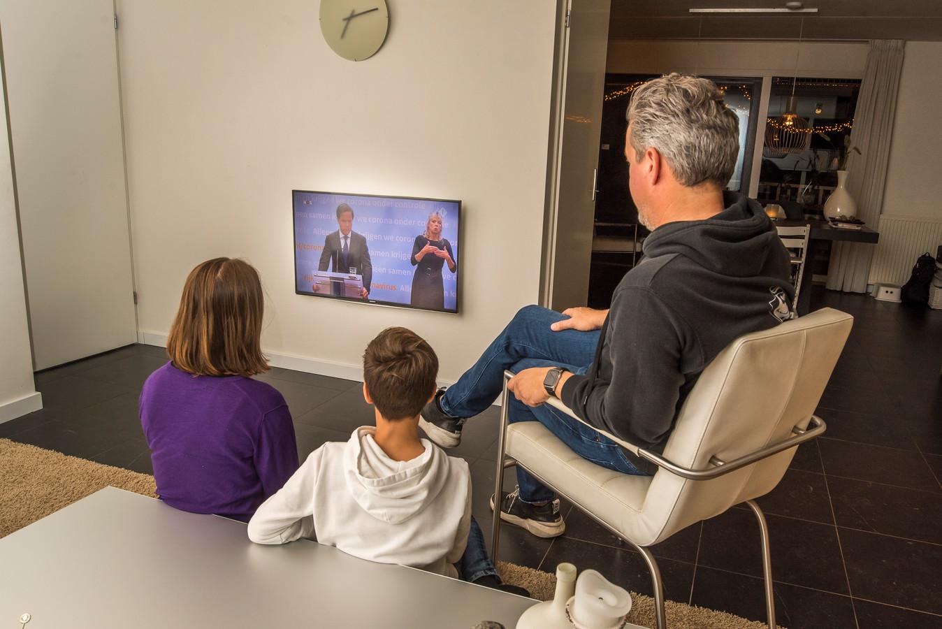 Directeur Johan de Jong van Metropool bekijkt de persconferentie van premier Rutte, samen met zijn kinderen Lena en Silvan.