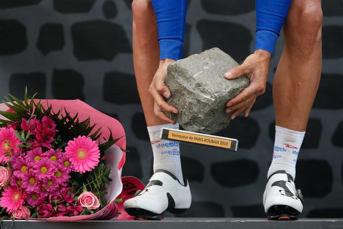 Winnaar Philippe Gilbert rapt de kassei op, de trofee die hoort bij de wielerklassieker Parijs Roubaix.