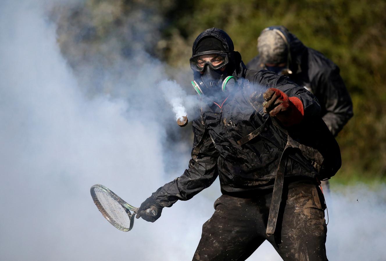 Een protestant gebruikt een tennisracket om zichzelf te verdedigen tegen traangasgranaten die zijn afgevuurd door de oproerpolitie bij schermutselingen bij het tien jaar oude kamp dat bekend staat als ZAD (Zone a Defendre – Zone) in de buurt van het Franse Nantes. Foto Stephane Mahe