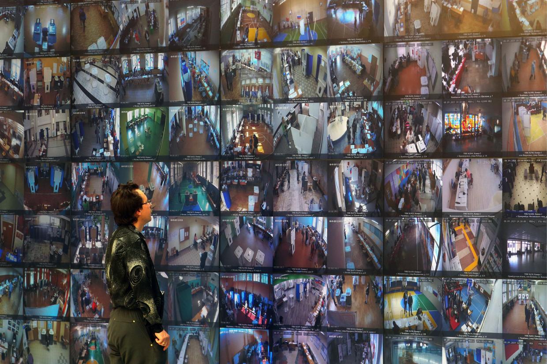 Op tientallen schermen zijn in het informatiecentrum van het Russische centrale kiescomité beelden uit stemlokalen te zien.