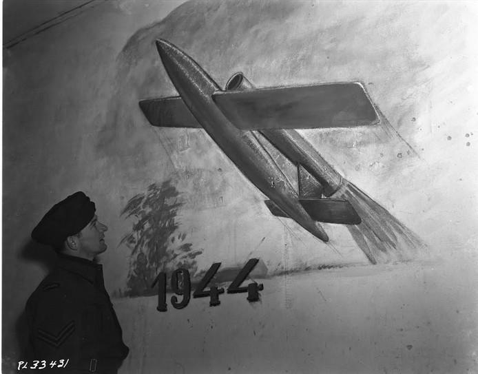Geallieerde militair bekijkt een muurschildering van een V-1 collectie.