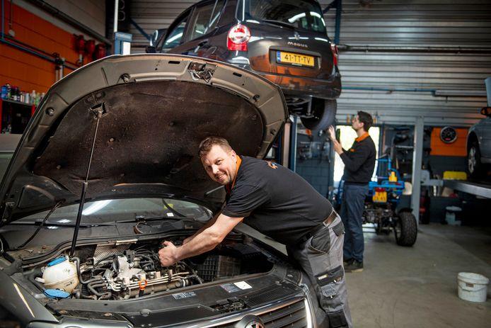 Dennis Schuiterd (voorgrond) en collega Justin ten Hove (achter) aan het werk in de garage.