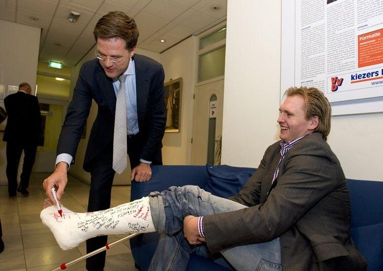 Mark Rutte zet zijn handtekening op het gebroken been van een partijlid Beeld null